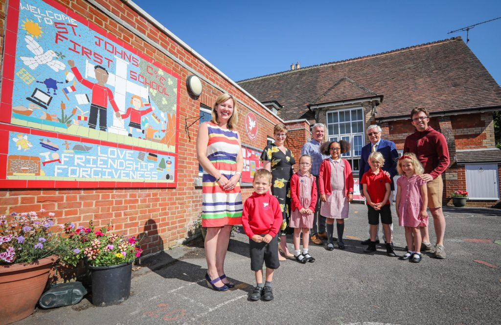 St John's Church of England First School celebrates a glowing SIAMS inspection. Headteacher Katharine Anstey is pictured with Wimborne Academy Trust CEO Liz West, Rev Peter Breckwoldt of St John's Church, WAT Chair of Trustees John Dickson, Kevin Metcalfe of St John's Church and pupils.