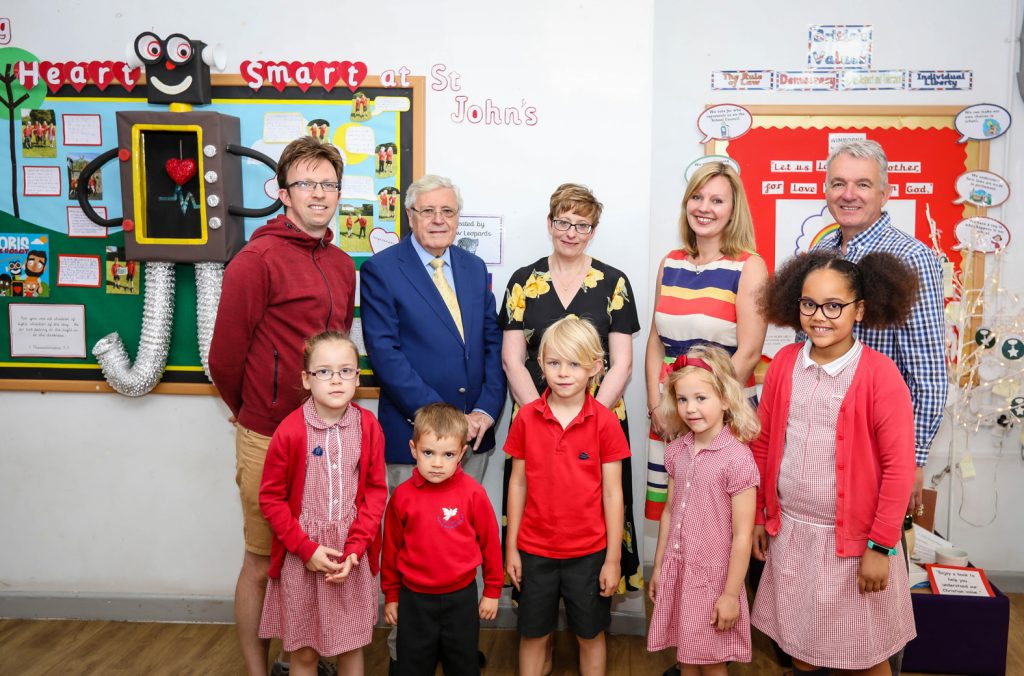 St John's Church of England First School celebrates a glowing SIAMS inspection report. Headteacher Katharine Anstey (second right) is pictured with Kevin Metcalfe of St John's Church, WAT Chair of Trustees John Dickson, Wimborne Academy Trust CEO Liz West, Rev Peter Breckwoldt of St John's Church and pupils.