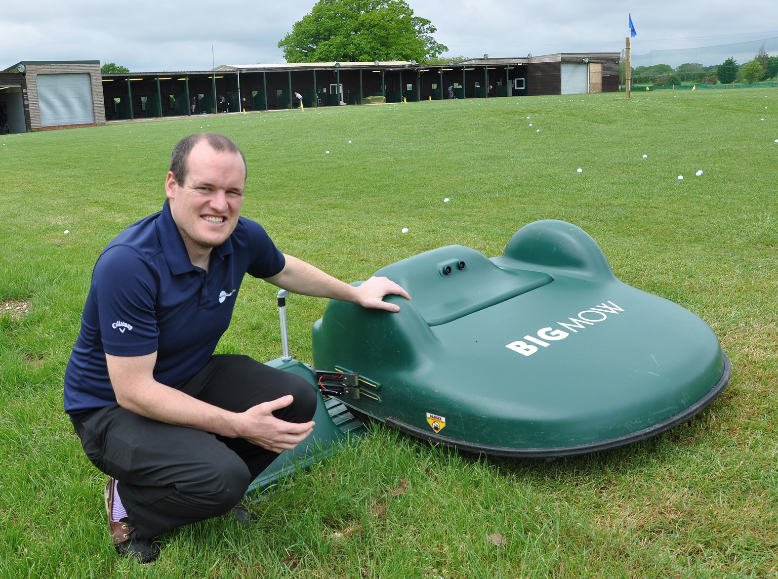 Daryl Dampney, manager of Parley Golf Centre, with the new robot that collects the grass on the driving range.
