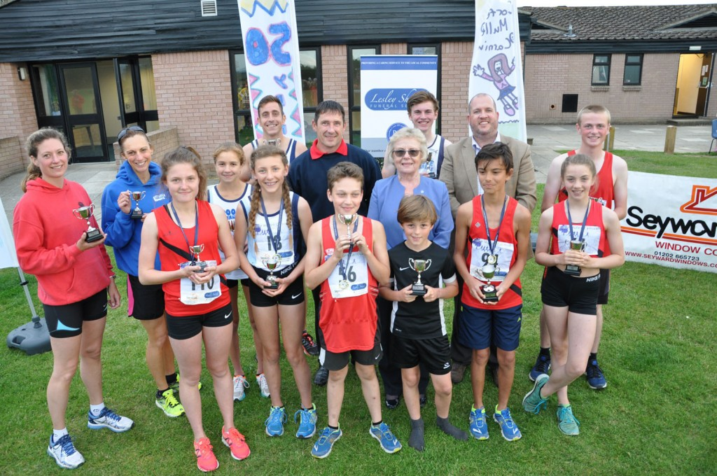 Wendy Percey of Lesley Shand Funeral Directors, centre, and Garry Dickerson of Seyward Window Ltd, blue top, and Cllr Paul Harrison representing the Corfe Mullen Parish Council, with the winners of the Corfe Mullen 5K and children's one mile run.