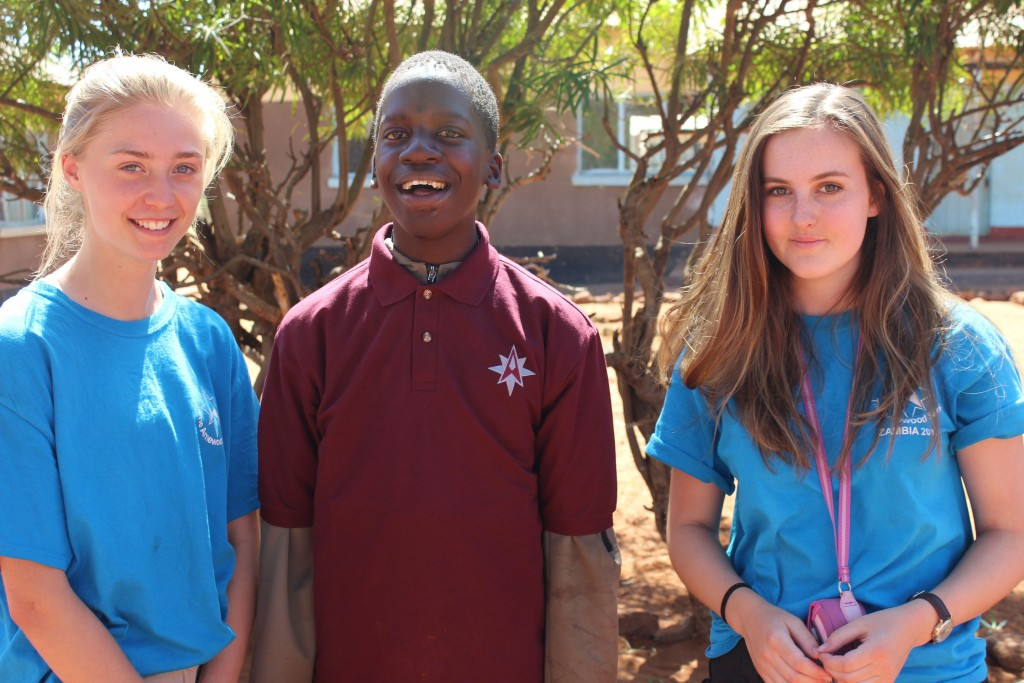 MAKING A DIFFERENCE: Arnewood students Annabelle Hill and Holly Gilbert hand over a donated Arnewood PE t-shirt to this 15 year-old Jacob from Hillcrest School in the Makuni village, Zambia. This was part of a three-week expedition to Zambia, Africa undertaken by 16 Arnewood students. This young Zambian's life was changed by the visit as the Arnewood students helped him to speak and write his name for the first time in his life.