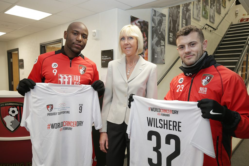 England and AFC Bournemouth player Jack Wilshere and striker Benik Afobe (with DCCF trustee Anne Rowland – centre) used World Cancer Day to highlight the work of Dorset Cancer Care Foundation (DCCF)