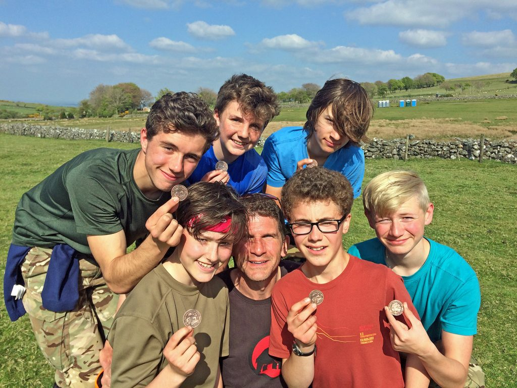 TRIUMPHANT: Oak Academy's Ten Tors team with teacher Dave Turner, just after they collected their medals for completing the gruelling two-day, 35 mile challenge.