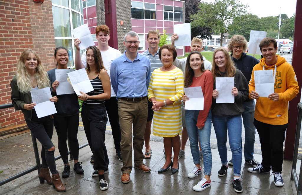 A-level results day: Arnewood students with (centre) Nigel Pressnell, headteacher, Mark Colman (head of sixth form) and chair of Governors Elizabeth Cook.