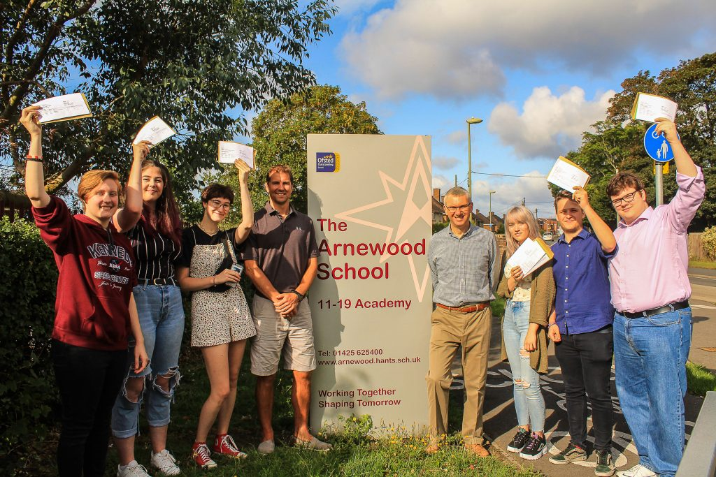 Headteacher Nigel Pressnell (centre right) and Head of Sixth Form Mark Colman (centre left) celebrate another successful year of A l-level results wth some of The Arnewood School's sixth formers.