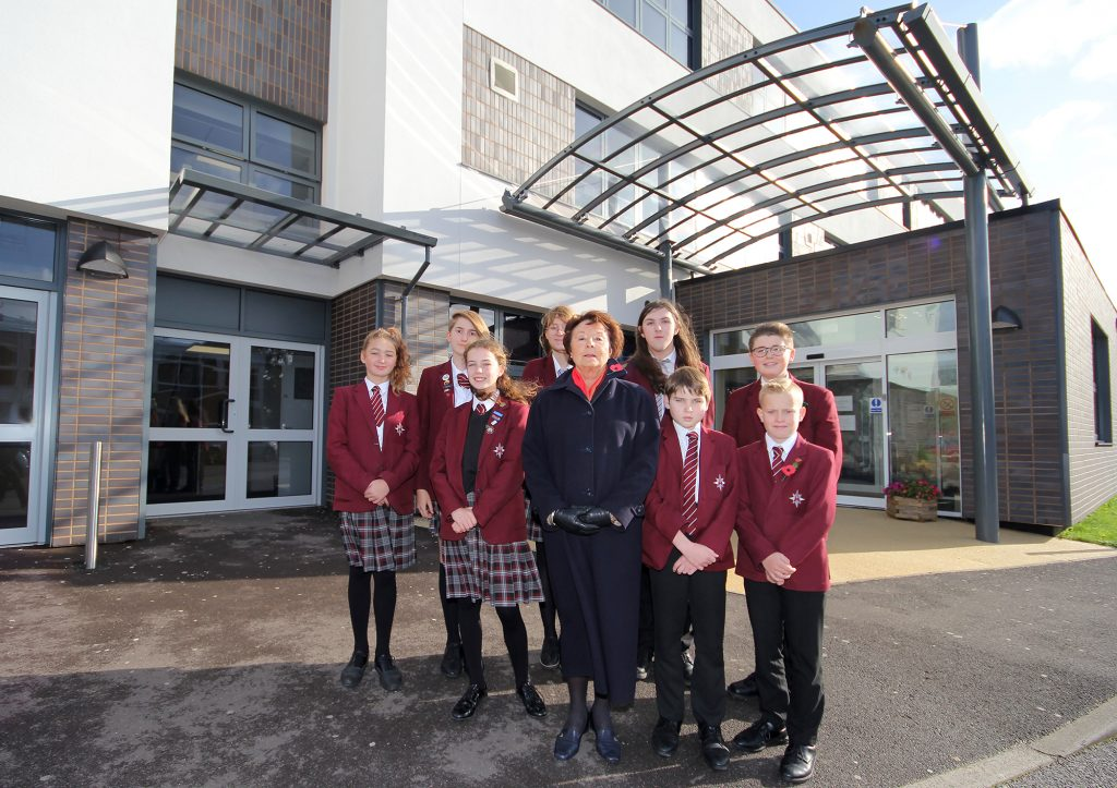 The Arnewood School has named its newly refurbished building after its chair of governors, Elizabeth Cook. Here she is pictured outside of the building with some of the students.